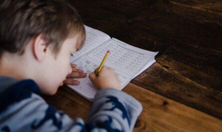 Malý chlapec píše číslo Pí do školního sešitu.