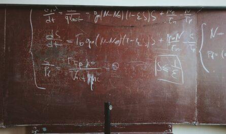 Zlomky jako součást příkladu napsaném na školní tabuli.